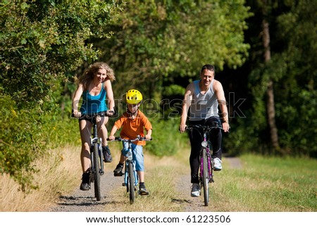 Family with child on their bikes on a summer day in sport outfit, FOCUS ON SON ONLY