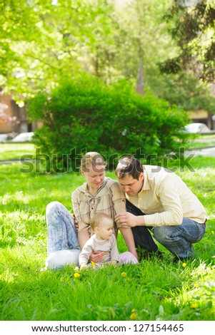 Family with child play in the park on green grass