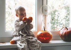 Family with child preparing for Halloween. Cute little girl sitting near window with carving pumpkin head jack lantern and halloween decoration at home.