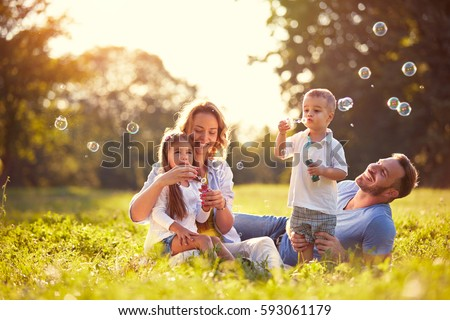 Family with children blow soap bubbles outdoor #593061179