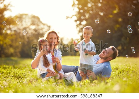 Family with children blow soap bubbles outdoor - Shutterstock ID 598188347