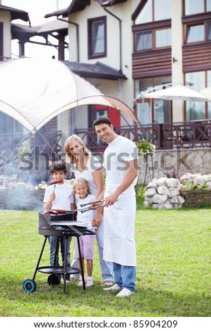 Family with children does barbecue - stock photo