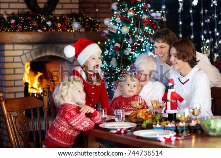 Family with children eating Christmas dinner at fireplace and decorated Xmas tree. Parents and kids enjoy festive meal. Winter holidays celebration and food. Grandmother cooking roasted turkey.