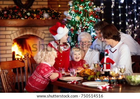 Family with children eating Christmas dinner at fireplace and decorated Xmas tree. Parents and kids enjoy festive meal. Winter holidays celebration and food. Grandmother cooking roasted turkey.  #750514516