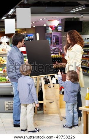 Family with children in shop look at an empty board