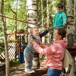 Family with children in the amusement park. Mom helps the baby stay on the obstacle course