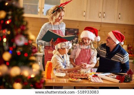Family with children preparing cookies for Xmas in kitchen