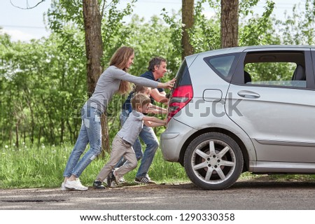 family with children pushing a faulty car
