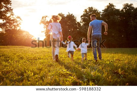 Family with children running together in nature, back view #598188332
