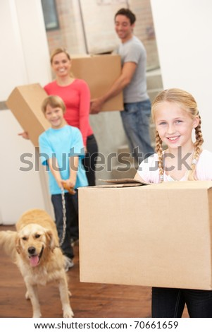 Family with dog on moving day carrying cardboard boxes
