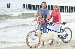 Family with dog riding a tandem bicycle at the beach
