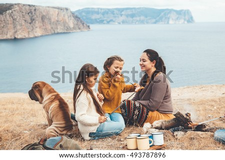 Family with dog sitting by the fire and frying sausages in mountains on the sea shore. Autumn hike in cold weather. Warming and cooking near flame together.