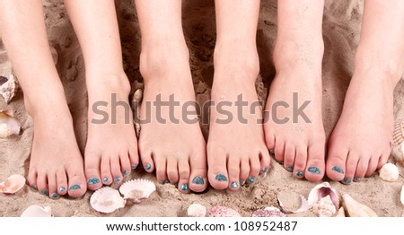 Family with feet in the sand with sea shells