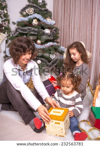 Family with gifts near a Christmas tree. Mom with kids opening presents under the Christmas tree