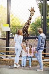 Family with giraffe in zoo