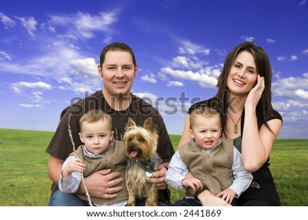Family with green field and blue sky background
