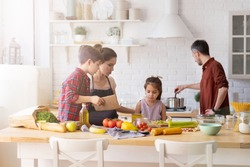 Family with kid spending time on home kitchen in morning. Parent children cooking. Mother and boy son talking to upset daughter. Father mixing boiling dish in pot on stove. Fresh vegetable on table