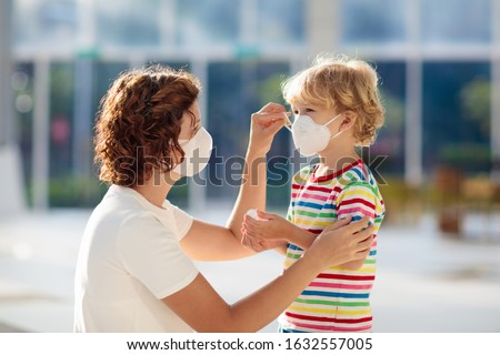 Photo of Family with kids in face mask in shopping mall or airport. Mother and child wear facemask during coronavirus and flu outbreak. Virus and illness protection, hand sanitizer in public crowded place.