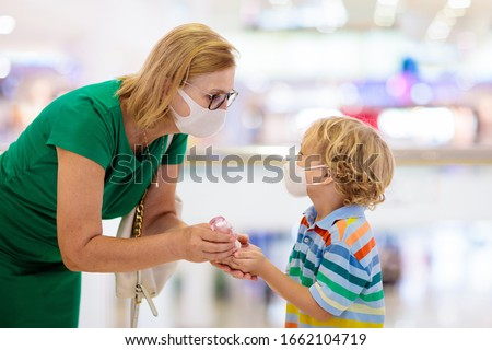 Family with kids in face mask in shopping mall or airport. Mother and child wear facemask during coronavirus and flu outbreak. Virus and illness protection, hand sanitizer in public crowded place.