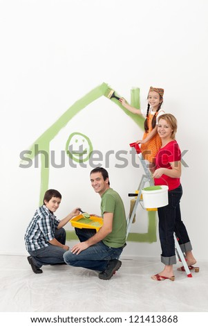 Family with kids redecorating their home - smiling with painting utensils - stock photo