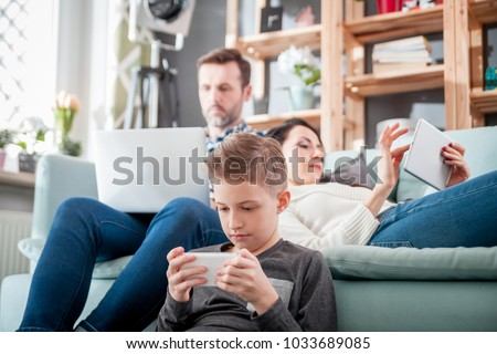 Family with laptop, tablet and smartphone at home, everyone using digital devices
