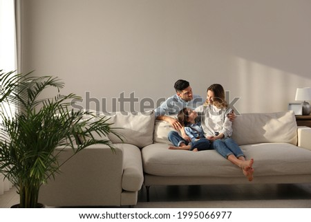 Family with little daughter resting on sofa in living room