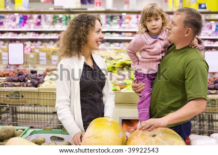 family with little girl  buy pumpkin in supermarket - stock photo