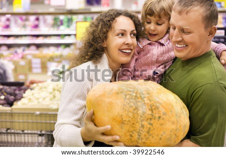 family with little girl  buy pumpkin in supermarket