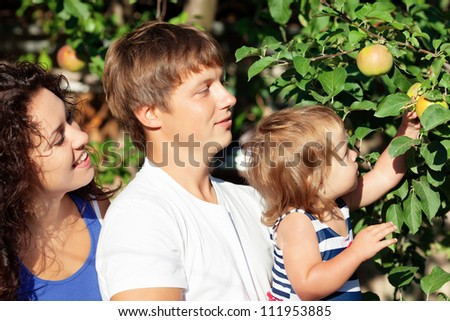 Family with little girl in apple garden