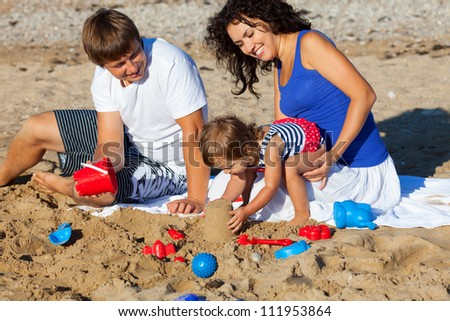 Family with little girl playing on the beach #111953864