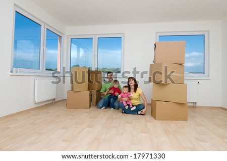 Family with moving boxes in new home. - stock photo