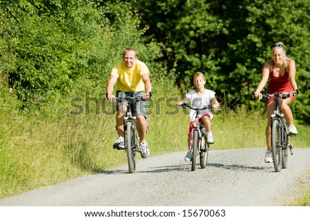 Family with one child riding their bicycles on a summer day