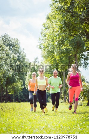 Family with personal Fitness Trainer jogging on a meadow #1120978751