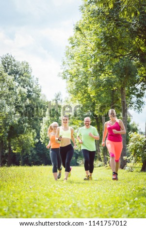 Family with personal Fitness Trainer jogging on a meadow #1141757012