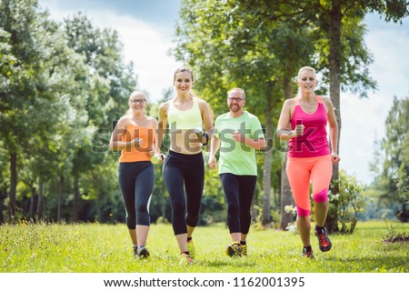 Family with personal Fitness Trainer jogging on a meadow #1162001395