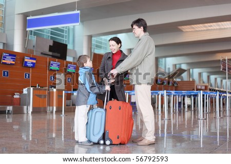 family with red suitcase standing in airport hall