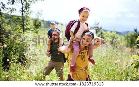 Family with small children hiking outdoors in summer nature.