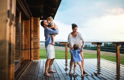 Family with small children playing in rain on patio by wooden cabin, holiday in nature concept.