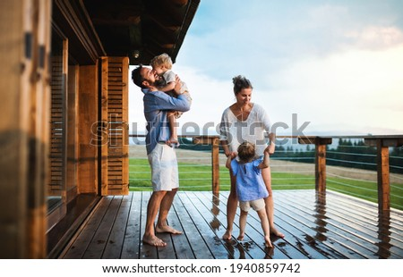 Family with small children playing in rain on patio by wooden cabin, holiday in nature concept. Photo stock ©