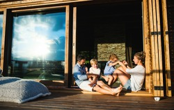 Family with small children sitting on patio of wooden cabin, holiday in nature concept.