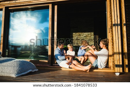 Family with small children sitting on patio of wooden cabin, holiday in nature concept. Photo stock ©