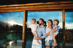 Family with small children standing by wooden cabin, holiday in nature concept.