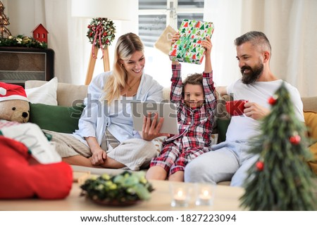 Family with small daughter indoors at home at Christmas, having video call.