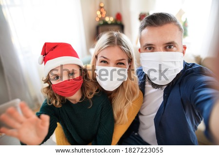 Family with small daughter indoors at home at Christmas, taking selfie with face masks.