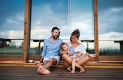 Family with small daughter sitting on patio of wooden cabin, holiday in nature concept.