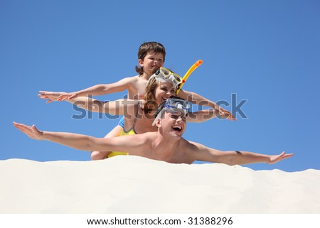 family with son lying on sand with hands up - stock photo
