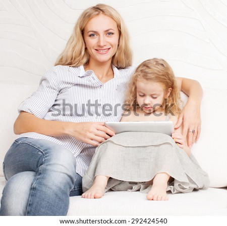 Family with tablet at sofa. Woman and baby with tablet computer. Mother and daughter at home on sofa