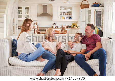 Family With Teenage Children Relaxing On Sofa Together