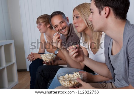 Family with teenage children sitting together on a couch eating popcorn and watching the television