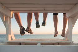 Family with their feet hanging at sunset in Cape Cod